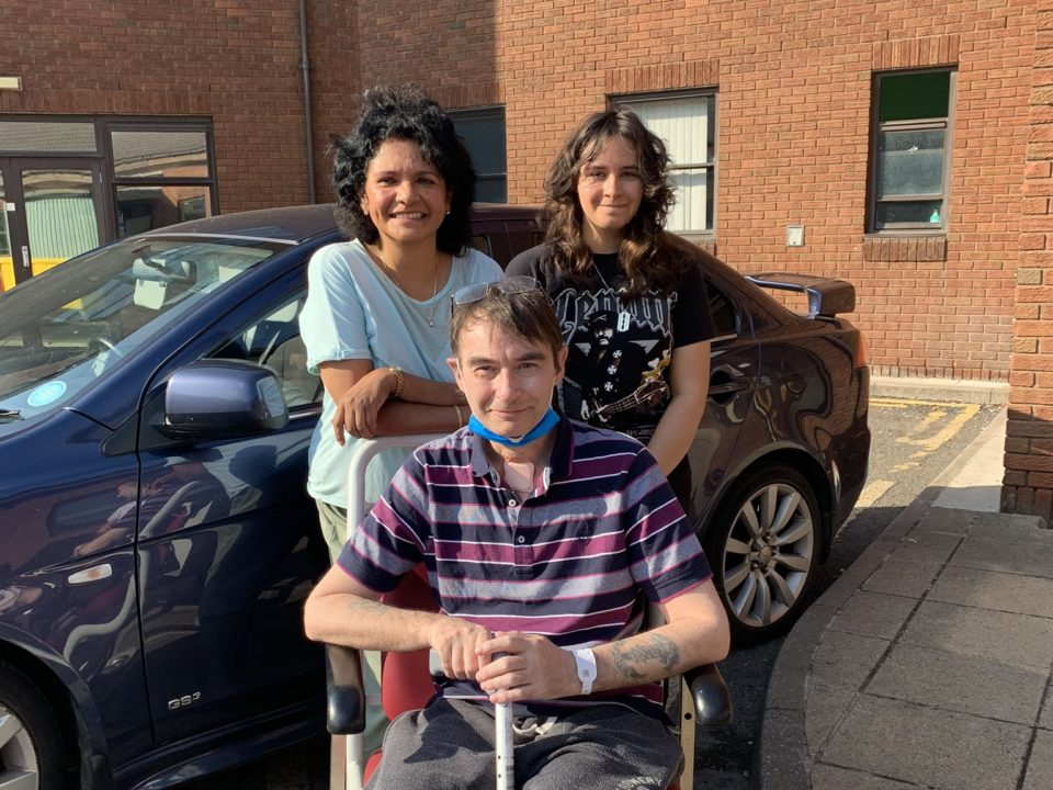 Family of three outside. Mother and daughter behind father, who is sitting in a wheel chair.
